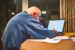 Elderly man of 93 years having trouble using his computer to check his finances online,very challenging for old people.