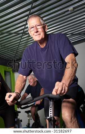 Elderly man on bike in the gym
