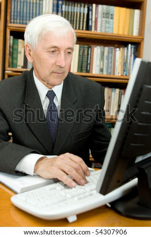 Elderly man peers into monitor of the computer