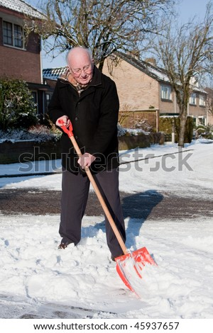 Elderly man removes snow from the street