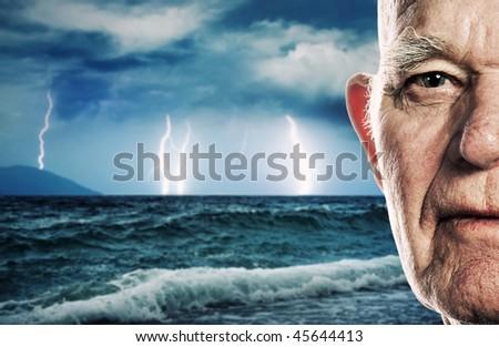 Elderly man's face over stormy ocean background