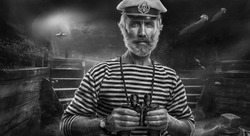 Elderly man sailor with binoculars on background of ocean
