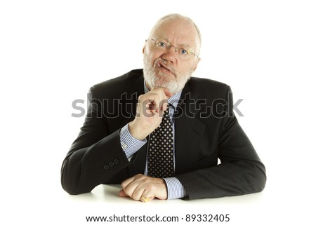 Elderly man sitting behind white desk and expressing how much he is bored
