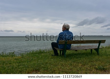 Elderly man sitting on an old wooden bench above the see in a cloudy day, contemplating the nostalgic sea-view