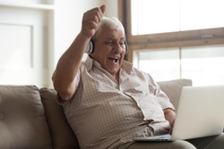 Elderly man sitting on couch watching online sport match on pc scream with joy feels excited celebrating football team victory, old male in headphones using apps singing aloud favourite song concept