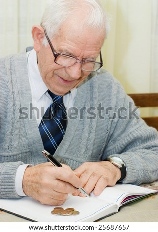 Elderly man sitting on the table and making a financial plan