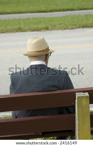 elderly man sitting on wooden bench waiting for a bus