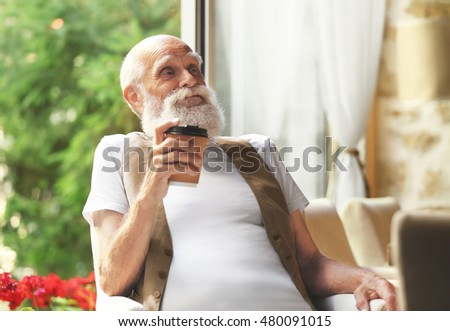 Elderly man sitting with coffee  in a armchair #480091015