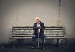elderly man sleeps sitting on a bench