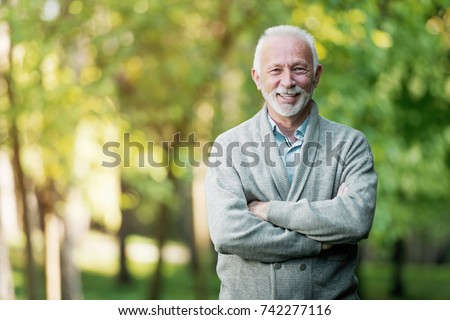 Elderly man smiling outdoors in nature  #742277116