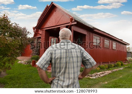 elderly man standing  back at the country house