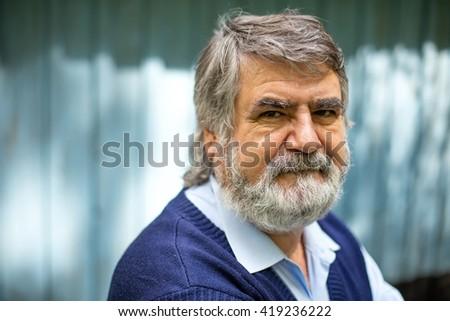 elderly man standing outside on blue wooden background #419236222