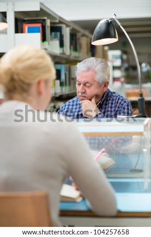 Elderly man studying among young college students in library and taking notes