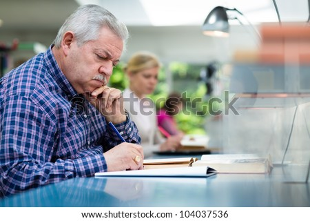 Elderly man studying with a group of young college students in library and taking notes - stock photo