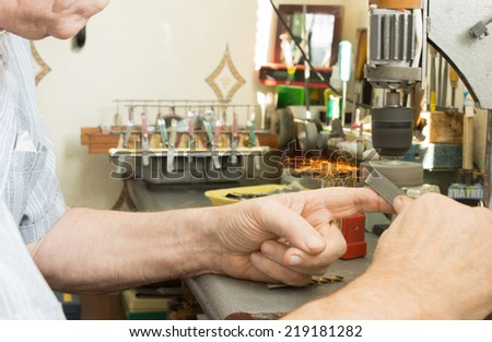 Elderly man using a small electric bench grinder to sharpen a tool or grind down a metal bar as he sits at his workbench