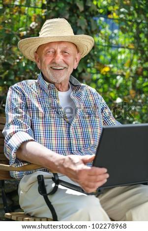 Elderly man using laptop in the park