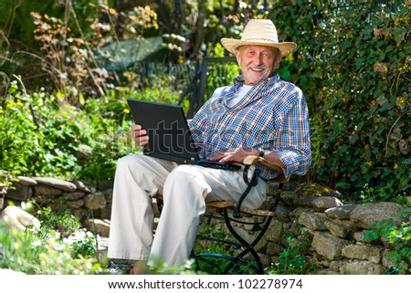 Elderly man using laptop in the park