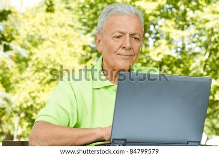Elderly man using laptop in the park.