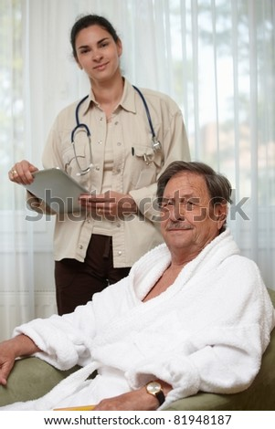 Elderly man waiting for examination, young female doctor at background.?
