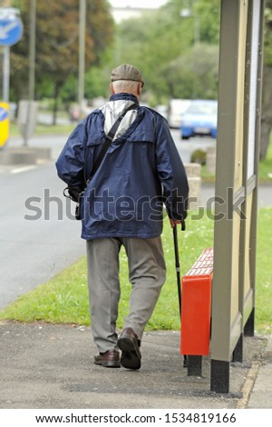 Elderly man walking with a walking stick to the bus stop.  South East London,UK.