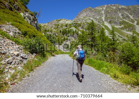 elderly man with a backpack goes on the road to the mountains