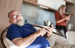 elderly man with a smartphone sitting in a home chair.