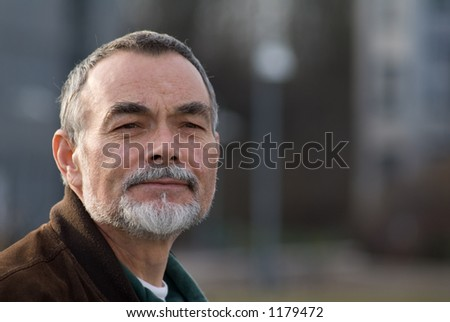 elderly man with beard in brown jacket