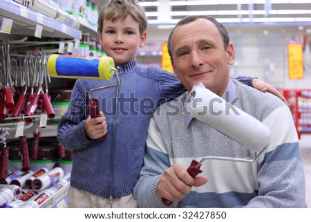 elderly man with  boy in shop with painting rollers in hands - stock photo