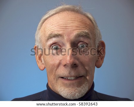 Elderly man with expression of amazement on blue background