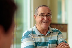 elderly man with glasses smiling, narrow focus,