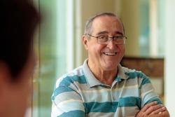 elderly man with glasses smiling, narrow focus, nice smile