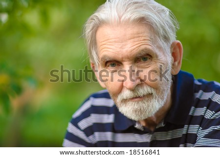 Elderly man with grey-haired beard close up against personal plot.
