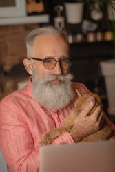 Elderly man with his cat working on laptop, smiling, looking at screen.