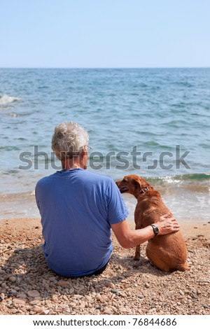 Elderly man with his dog at the summer beach