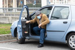Elderly man with protective mask goes out with fatigue from his car. Concept of old age and difficulty of movement