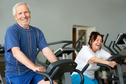 Elderly man working out on exercise bike in gym. Retired caucasian man looking at camera while exercising at fitness club. Training for long living.
