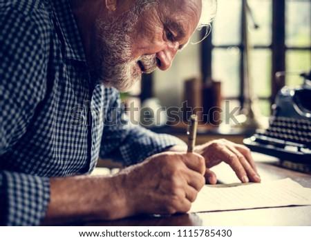 Elderly man writing a letter
