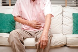 Elderly men have abdominal pain sitting on the sofa in the house. Concept Problems of the digestive tract in older people, health care
