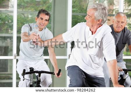 Elderly men on bikes with water in fitness center