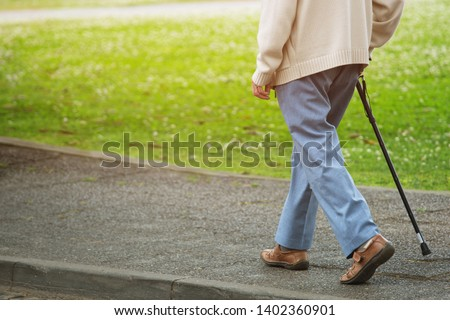 elderly old man with walking stick stand on footpath sidewalk crossing the street alone roadside in public park. concept senior across the street. soft focus #1402360901