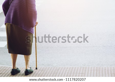 elderly old woman with walking stick stand waiting on footpath sidewalk crossing the street alone. concept senior across the street to zebra crosswalk.