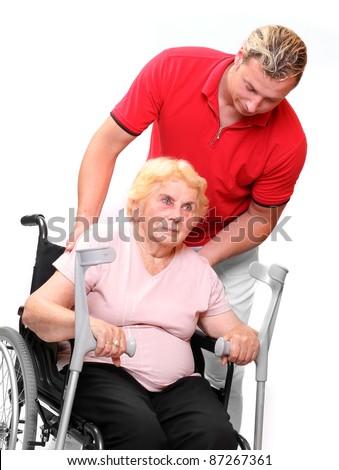 Elderly paraplegic woman sitting in a wheelchair and her male nurse.