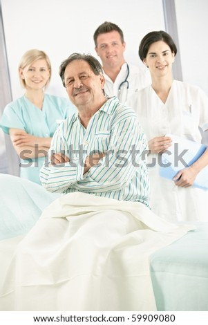 Elderly patient in hospital smiling at camera with medical team in background.?