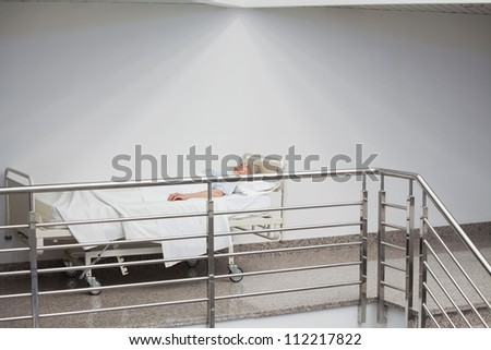 Elderly patient sleeping in the corridor in hospital hallway