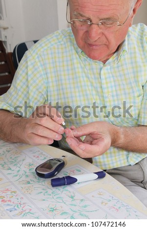 Elderly pensioner wearing glasses taking a small blood sample from his fingertip for use on his glucometer