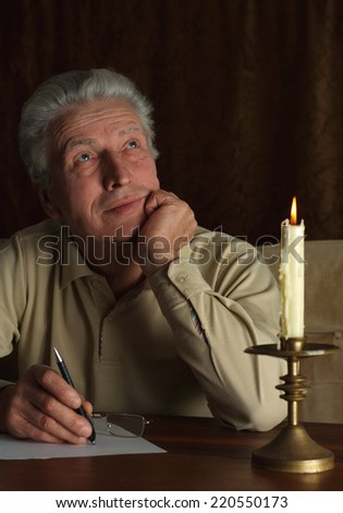 Elderly pensive man writes a letter by candlelight