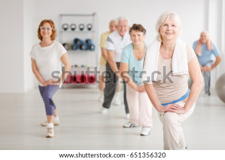 Elderly people exercising in a group in fitness club