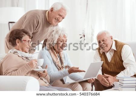 Elderly people using computer, sitting in light room