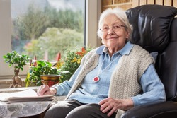Elderly Person with Emergency Button Sitting in the Living Room