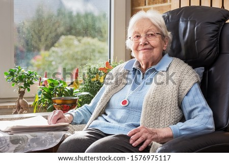 Elderly Person with Emergency Button Sitting in the Living Room Foto d'archivio ©